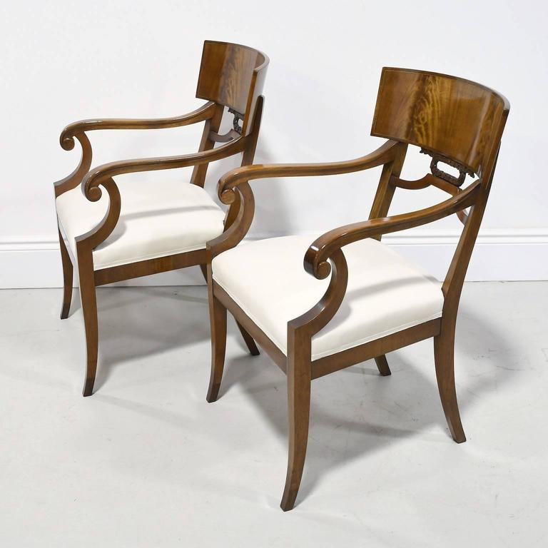 A very handsome and refined pair of Karl Johan-style Empire Klismos armchairs with saber legs from the Art Deco period in Sweden, circa 1920s. These chairs are exquisitely made using Cuban mahogany, Fine joinery techniques, and offer a wider seat