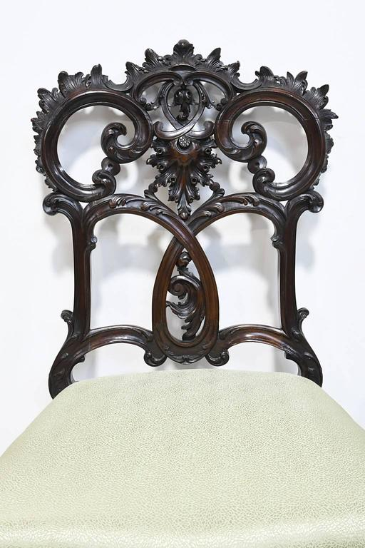 An exquisite pair of very finely carved Rococo-style chairs in mahogany with elaborate rocaille embellishments throughout. The high quality and well articulated carving suggest that they are NY made and can be attributed to or were influenced by the