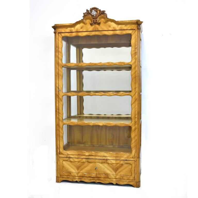 A very lovely display cabinet or vitrine in cherrywood with original glass door, glass side panels and mirrored back, with carved bonnet. Offers one storage drawer with working lock and key. Germany, circa 1850.  Measures: 38 1/2