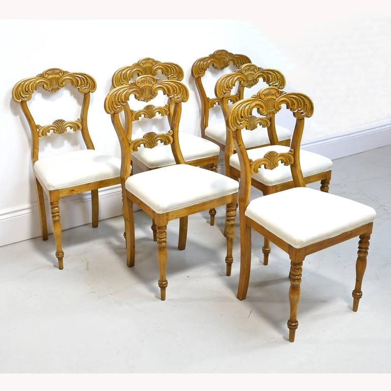 From the reign of the French-born Swedish king, Karl Johan, a very lovely set of six dining chairs in birch with foliate carvings on crest and bottom back rail, with turned front legs and saber back legs and upholstered seat, Sweden, circa