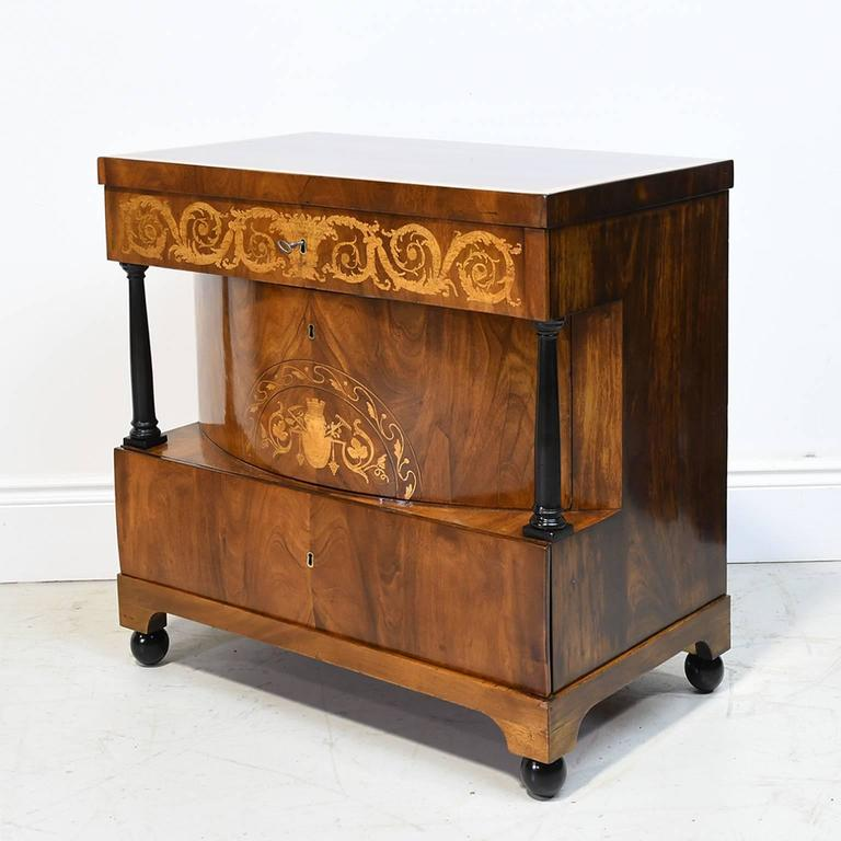 A very fine Biedermeier parcel-ebonized mahogany commode with top above a single drawer floridly inlaid with scrolling acanthus marquetry, the second convex-drawer inlaid with a scrolling foliate lunette and flanked by ebonized columns, and the