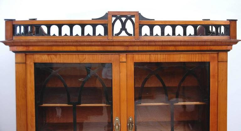 An Austrian or German Bavarian Biedermeier vitrine in cherrywood with carved, open fretwork gallery, with ebonized details above crown molding. Arched Gothic style tracery work on interior of glass doors is ebonized as are various moldings