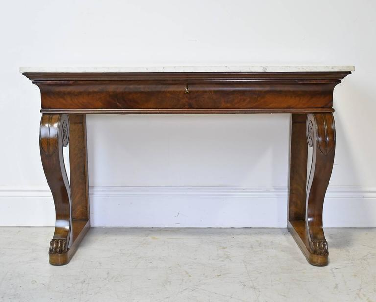"A very handsome French Empire console table in mahogany with white carrara marble top, offering one long storage drawer and resting on a base with ""S"" scrolled leg supports with well-articulated carved lions' paw feet, France, circa"