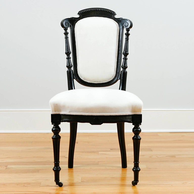 A handsome and very comfortable set of four French dining chairs with upholstered back and seat. Ebonized frame has carved crest and apron, turned front legs with casters and turned back spindles. From the reign of Napoleon III, France, circa