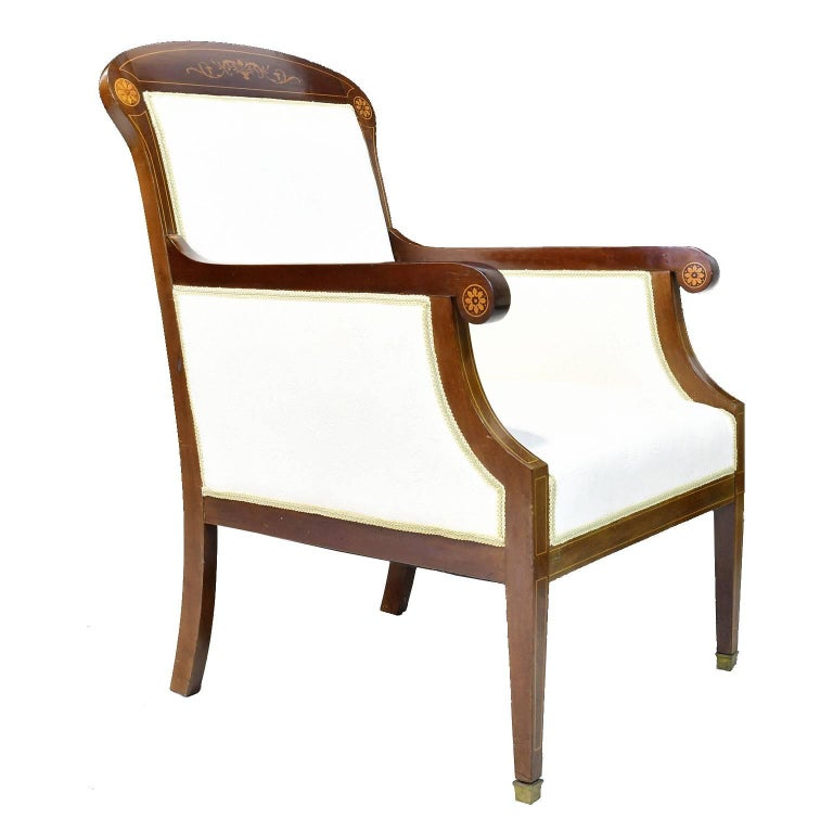A very fine pair of bergères in beautiful West Indies mahogany with upholstery. Frame has fine inlays in satinwood of pinwheels on the scrolled arms and corners of the rounded crest flanking the center swag with foliate inlays. Chairs rest on