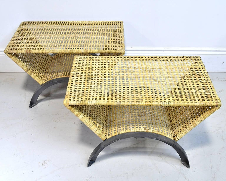 Pair of end tables or stools with top and arched bottom shelf in natural-colored woven rattan, and resting on arched demilune legs in gunmetal finish.
