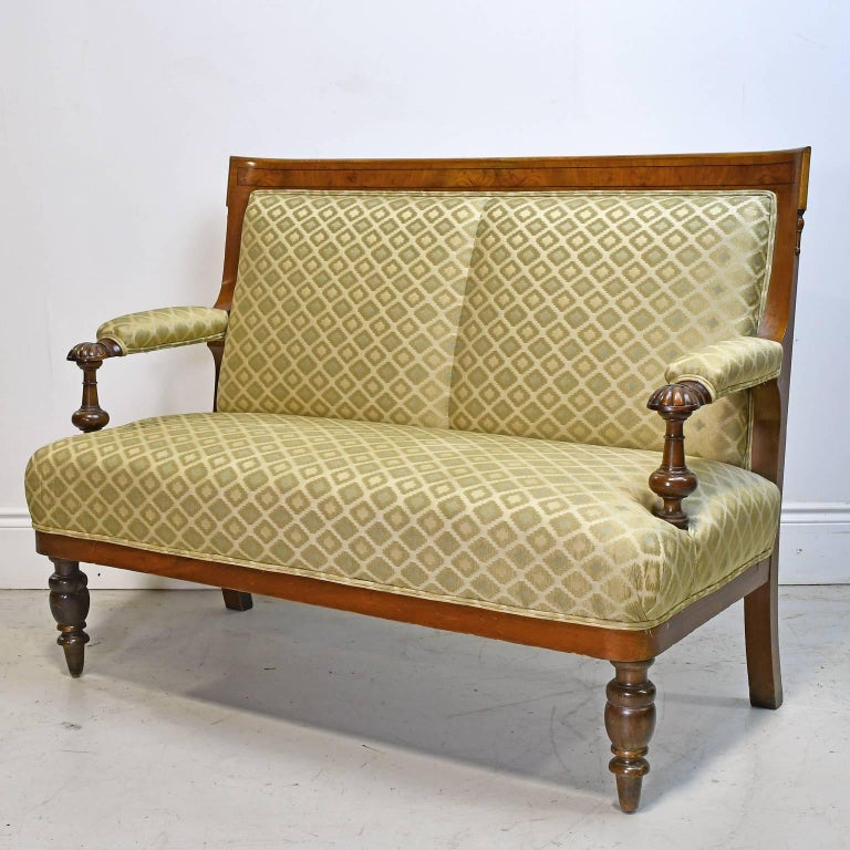 A small and comfortable canape or settee in figured walnut with ebonized inlaid banding. Legs are turned out of beechwood and stained. Offers upholstered arm rests, back and seat, with eight-way, hand-tied springs that have been pulled tight &