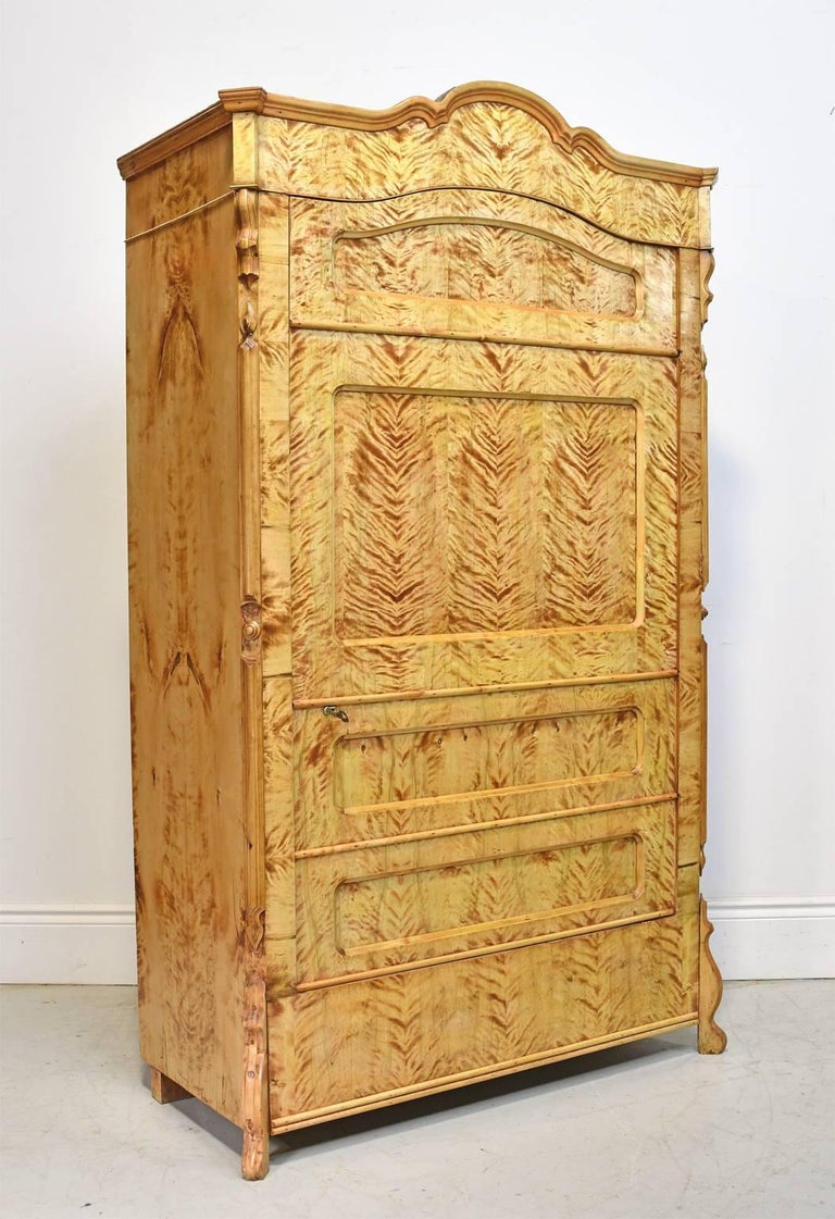 A very beautiful Biedermeier armoire or cabinet in a honey-colored fire birch that has been expertly book-matched throughout to showcase the singular beauty of its grain. The faux front of the single door is paneled to give the illusion of a