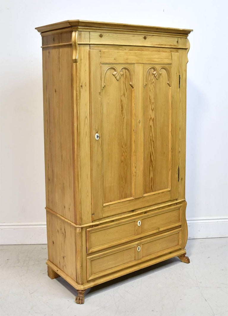 A charming country armoire in a light, honey-colored pine with one cabinet door opening to 3 interior, adjustable shelves, with two exterior bottom drawers. Denmark, circa 1835. Embellishments include two panels with double arches on the door,