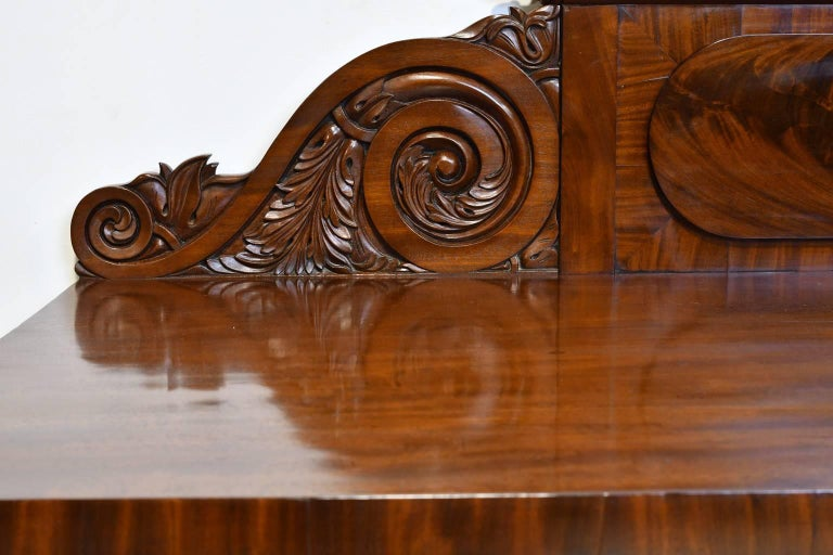A fine and elegant English Regency pedestal sideboard in mahogany with carved backsplash. Offers three convex silverware drawers spanning the length just below the top, with shelving on one pedestal and two celarette drawers on the other for storage