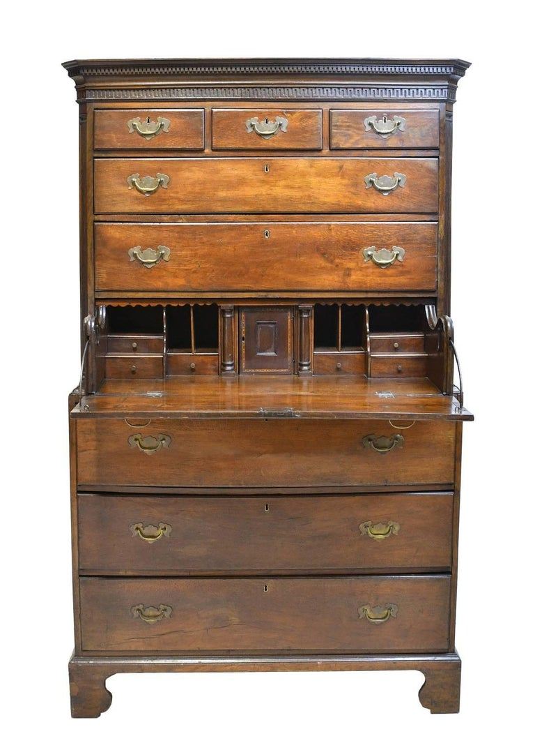 A very handsome early Georgian highboy or chest on chest with dentil moulded cornice above Greek-key moulding, with three drawers over six graduated drawers with original brass escutcheon plates and swan-neck bail handles. The bottom drawer of top