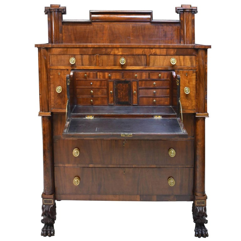 A beautiful example of an early American Empire chest with full-column front and stand-up butlers desk. Provides ample storage as a chest of drawers, and doubles as a secretary with additional small drawers in the interior. Rests on well-articulated