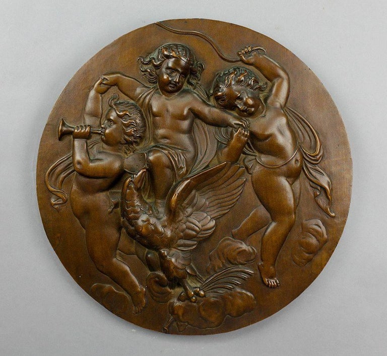 A pair of elaborate carved nutwood wall plates depicting putti riding on fishes and music playing putti with eagle, circa 1900. One plaque with signature: A. Lapicz. Sop 6/12 872.