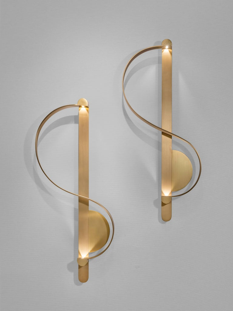 This pair of 'Clé De Sol' sculptural sconces by French-Lebanese Charles Kalpakian is produced entirely in gilded brushed brass. The design is inspired by the calligraphy of sheet music. In this wall light, the classic G Clef shape is transformed