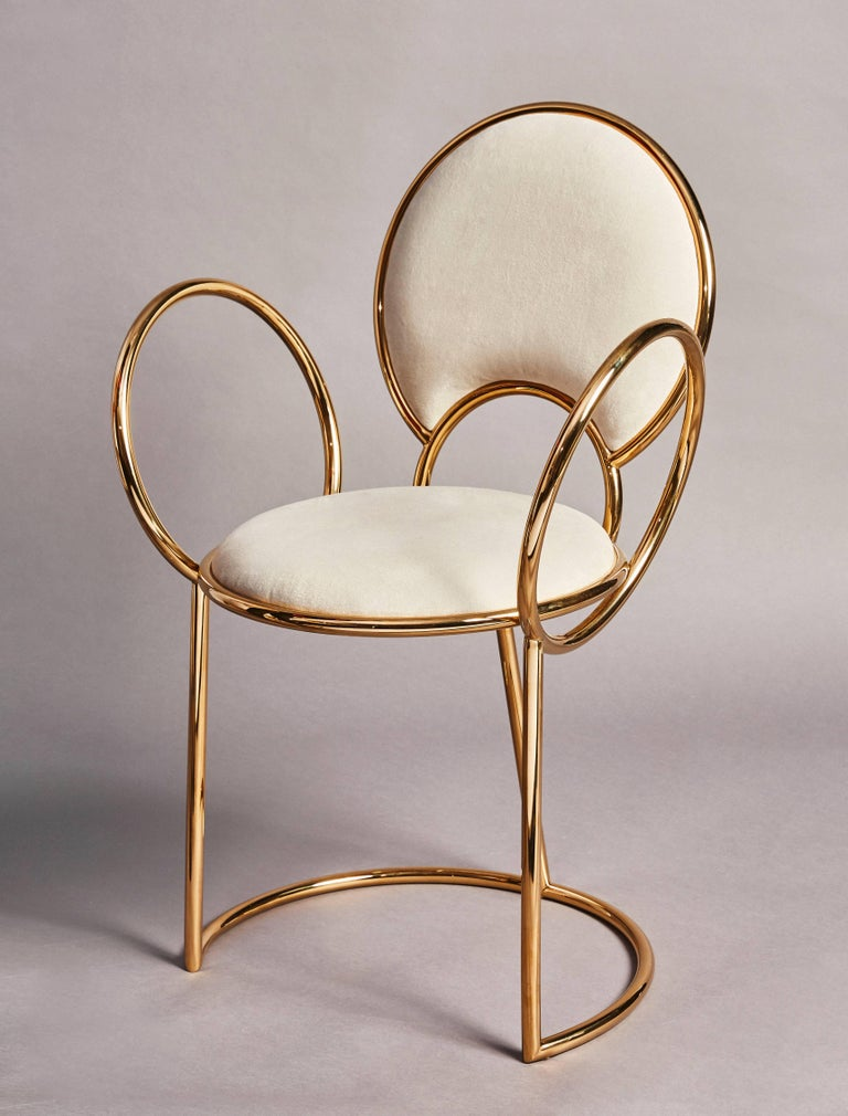 The 'Yue chair' by much acclaimed duo Studio MVW is entirely produced in anodized stainless steel with brass finish in a subtile gold pink shade. The delicate loop armrests completing the rounded light grey velvet covered seat and back make the