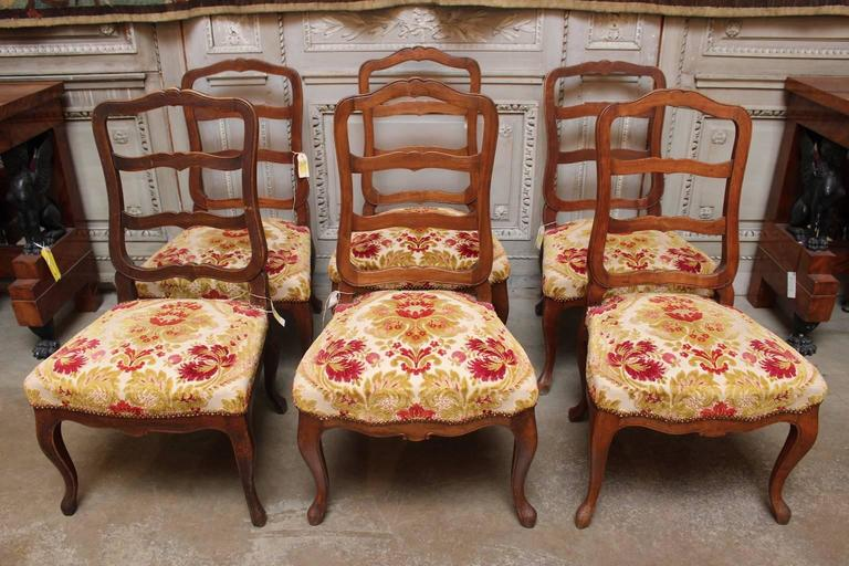 A set of six Swiss walnut dining chairs in the Louis XV style.