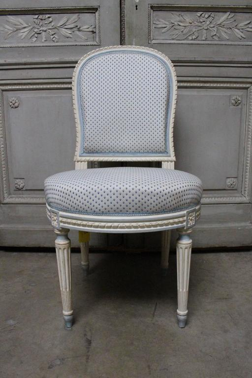 A suite of ten French Louis XVI style dining chairs in carved oak with a painted finish, based on a model by Jacob.