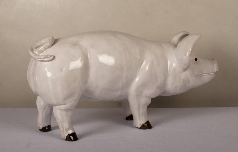 Glazed terra cotta pig with glass eyes, from the turn of the century, French.