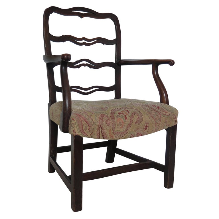 This is a very well-proportioned example of a mid-18th century, English George II period Country armchair made from elm.  It has a good ribbon-back splat with nicely carved ear pieces and a superb crook shaped arm.  The chair has a pegged and