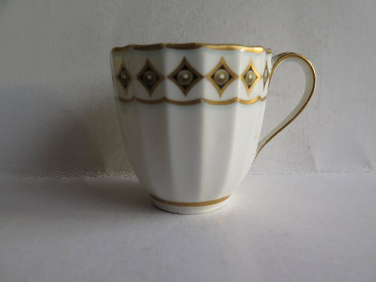 This is a very good early coffee cup by the Derby factory, made in the late 18th century, George 111rd period, circa 1790.  The body of the cup has 16 vertical flutes and has a plain loop handle.  It is decorated with gilt rims with the outer rim