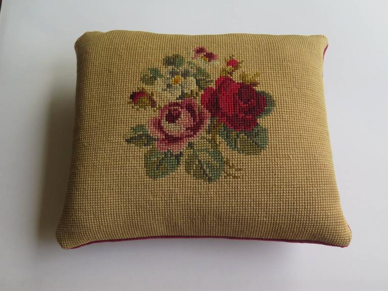 This is a small size, English, Art Nouveau inspired, Victorian needlepoint tapestry cushion or pillow from the late 19th century.   The hand worked design shows rich red, plum and soft pink rose plumes with green foliage on an old gold background
