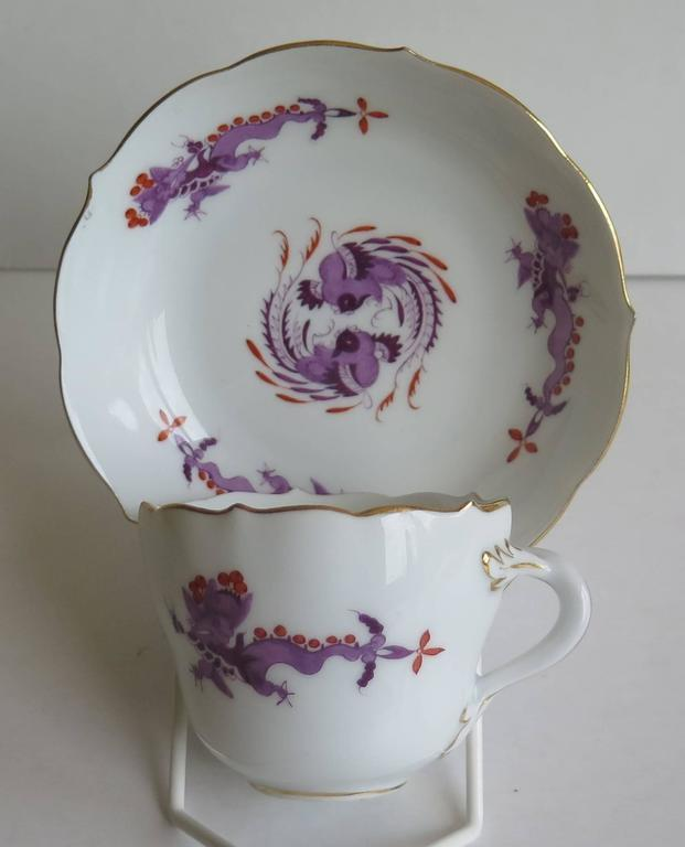 This is a small demitasse cup and saucer by the Meissen factory in fine white porcelain.  The cup and saucer both have wavy edges and the cup has a twisted branch handle with leaf attachments. They are beautifully decorated in a multi shaded purple