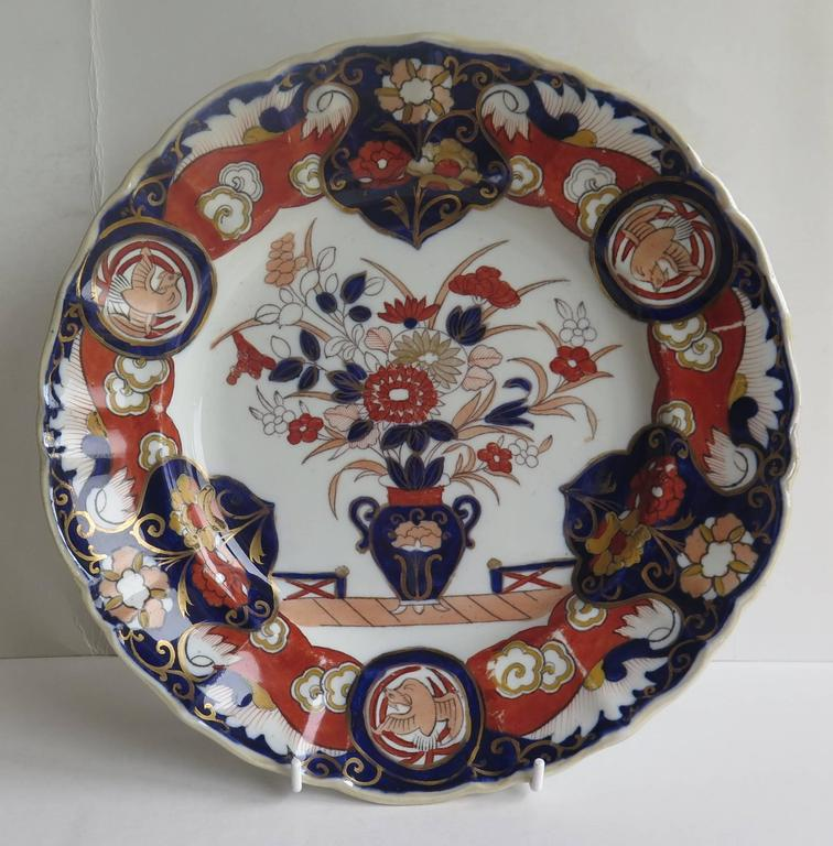 This is a very attractive large Dinner Plate made by the Mason's Patent Ironstone China Pottery Company in the early part of the 19th Century.  This plate is decorated in the: Fence Vase and Dove pattern, which shows a central flower filled vase,