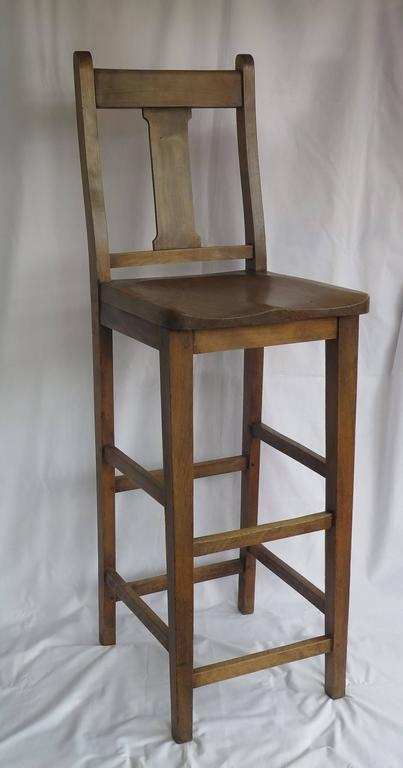 This is a late 19th century Clerk's Estate High Chair as used at a Clerk's Desk in the late Victorian period, circa 1880, now very useful as a kitchen chair at a breakfast bar.  The chair is made of beech with a shaped elm seat and a nicely curved