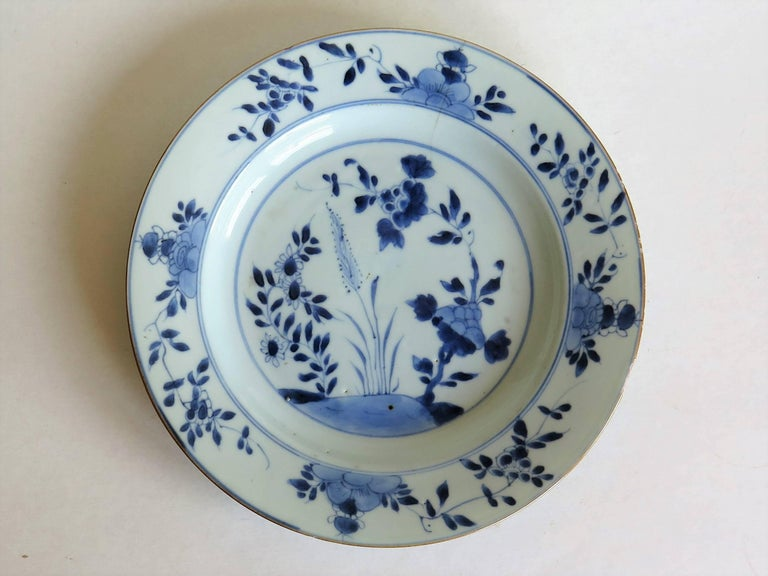 This is a good hand-painted Chinese Export porcelain plate, dating to the early / mid-18th century, circa 1720-1750, Qing dynasty.  The plate is well potted, and has been hand decorated in varying shades of cobalt blue. The glaze is thin and glassy