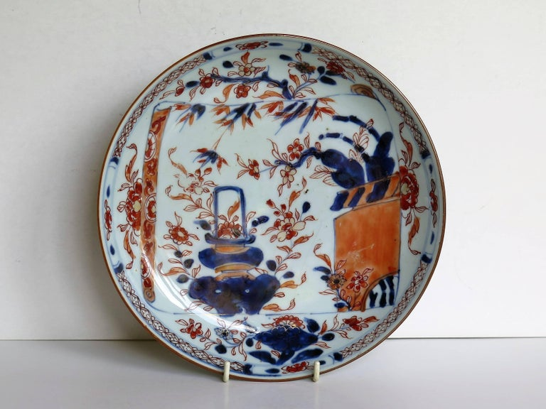 This is a fine hand-painted Chinese porcelain dish or plate with a deep well, dating to the early 18th century, circa 1720.  The glaze is thin and glassy with a soft light bluish tinge. The foot rim is fairly deep and neatly trimmed. There are no