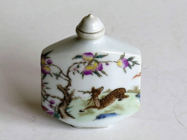 This is a very decorative, hand-painted, Chinese porcelain snuff bottle, circa 1940s.   The bottle has a low shaped foot and a nice tactile rectangular shape which curves to the front and back faces. It has a narrow neck with a cone shaped