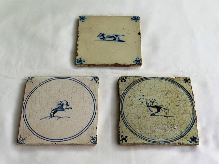 These are three individual delft earthenware tiles, all with a blue and white dog pattern, made in the Netherlands during the 18th century. 