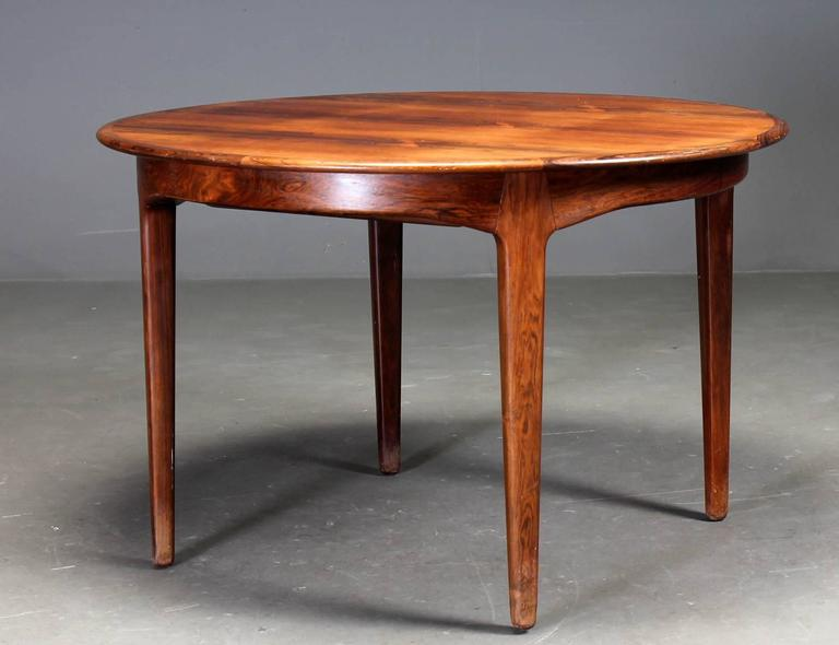 This round dining table extends to 275 cm was designed by Henning Kjaernulf in 1958 and made and labelled by Soro. The construction is extremely robust with each solid rosewood led sliding into slots in the apron of the table. This interlocking