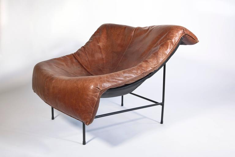Beautiful lounge chair designed by Gerard Van Den Berg for Montis, early 1980s. The name of the model is 'Butterfly'. The chair has a metal frame that carries a seating for very warm and soft cognac brown leather. The chair has a very relaxing and