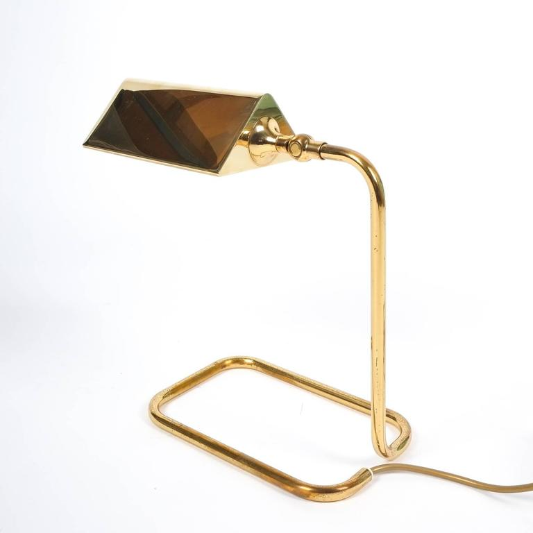 Nice table light by Koch Lowy, circa 1960 featuring a bent brass base and polished brass shade. It holds a single large bulb with 60W maximum and is in excellent condition.