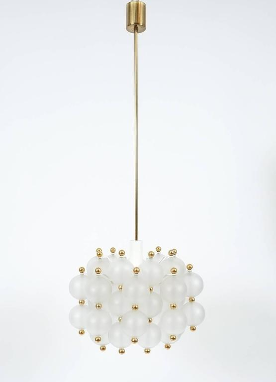 Glass chandelier lamp in the style of Seguso, circa 1980. Beautiful and large chandelier with a multitude of smooth translucent handblown glass balls with golden brass knobs. The fixture is in very good condition (fully restored) and holds a sinlge