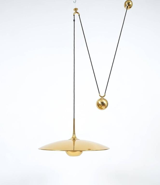 Elegant highly polished brass pendant by Florian Schulz/Germany with a shiny brass finish and heavy counterweight to easily adjust the light in height. Excellent condition, it holds one bulb with a max. of 100Watts. We have more pieces available by