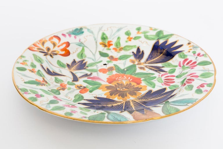 This is a 19th century porcelain plate with a floral design in shades of navy blue, green, gold and orange with a gold rim. It is in very good condition with only minor scratches.