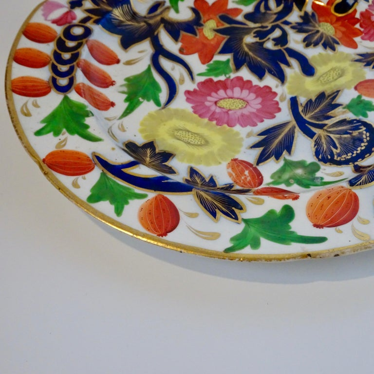 This is a 19th century porcelain plate with a decorative floral design in shades of blue, pink, yellow, orange, and green. It has a beautiful and bold design and is a stunning piece with only minor wear.
