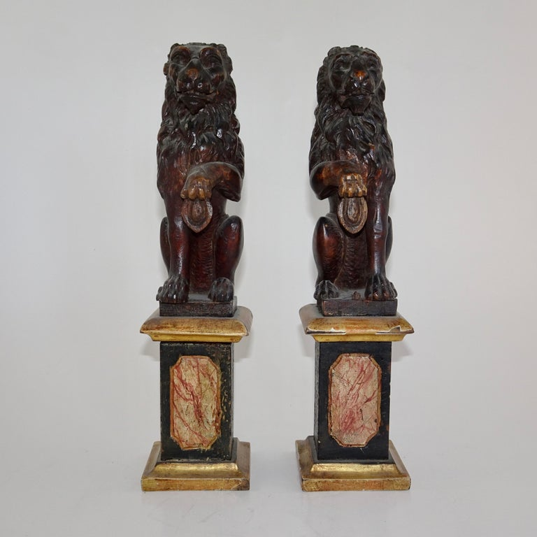 Pair of antique bronze Lion Statues on marble base. The lions are depicted sitting on their hind legs with one paw lifted. The marble base is in shades of gold, red, and black.