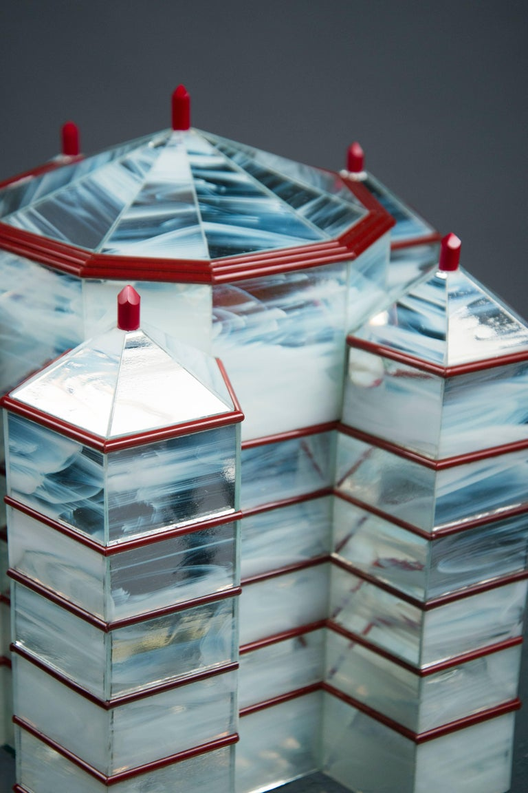 """Octagonal prism structure with five octagonal """"towers"""" at each corner. The milk-mirrored surface features horizontal carnelian red stripes as well as tips of the same colored glass. A glazed exotic wood interior is revealed under each of the six"""