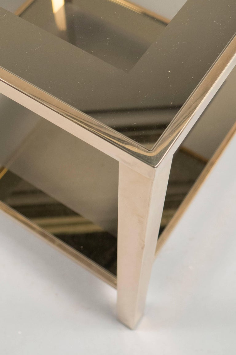 Square polished brass side tables featuring two smoked glass tops each.