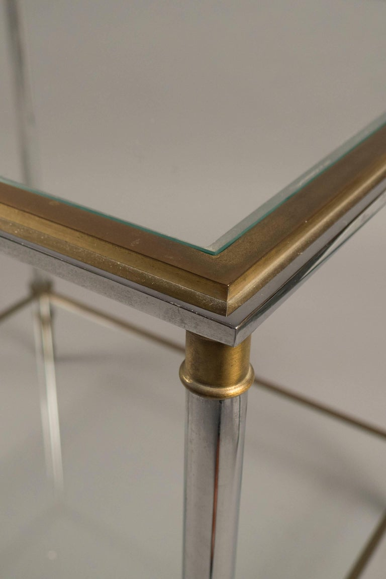 Polished steel and brass side tables, each featuring two tiers fitted with clear glasses.