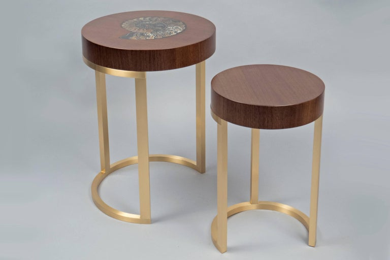 Brushed brass bases, supporting two round walnut veneered tops, the larger one featuring an inlaid ammonite. Available in macassar, walnut, mahogany and a variety of differently colored and sized ammonites. Each piece is unique to the natural