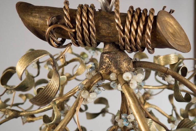 Green-brown patinated bronze chandelier in the shape of a mistletoe, featuring a roped off branch and numerous opaline glass pearls throughout.