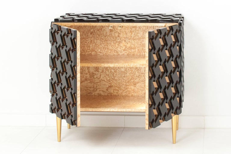 "Unique piece, featuring a houndstooth pattern made of apricot mirrored glass overlaid with rippled amber glass sections, raised on brass legs, which feature a leveling system. The blonde wood interior holds one shelf. Model ""pied de poule""."