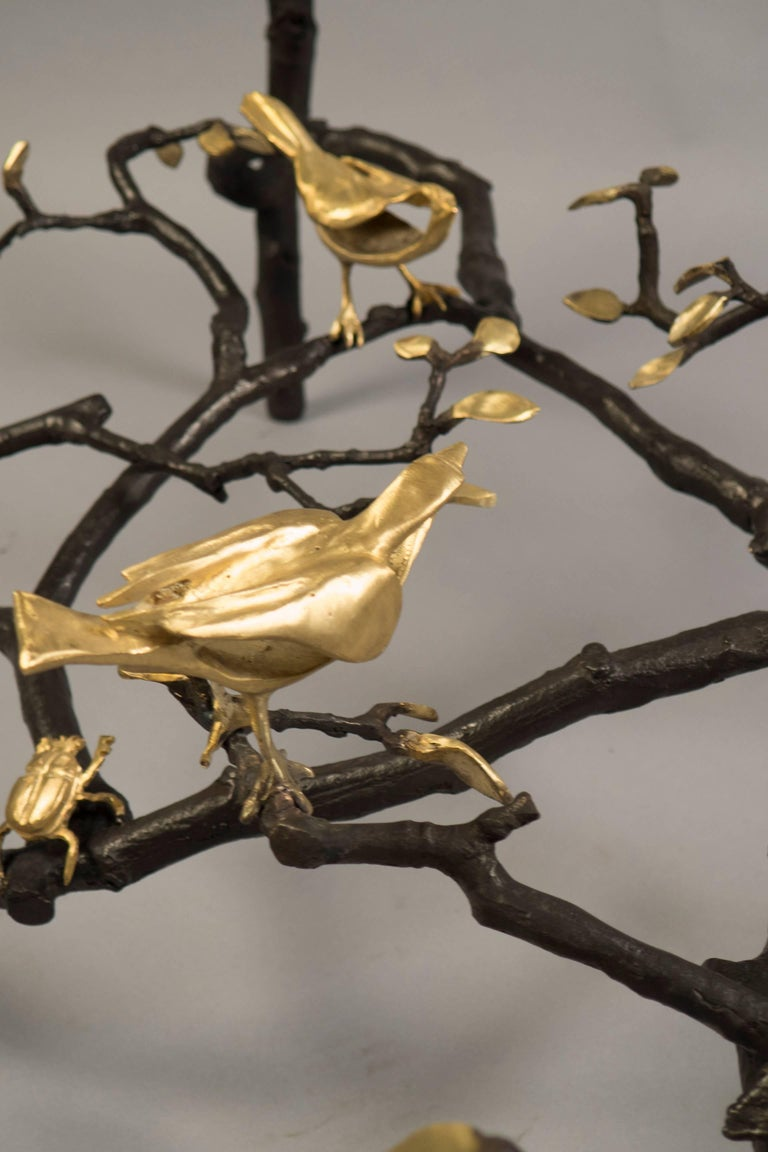 Wrought iron rectangular frame, braced with a sculptural stretcher depicting branches with birds, highlighted in gold leaf, and inset with a clear glass top. Signed on the base. 