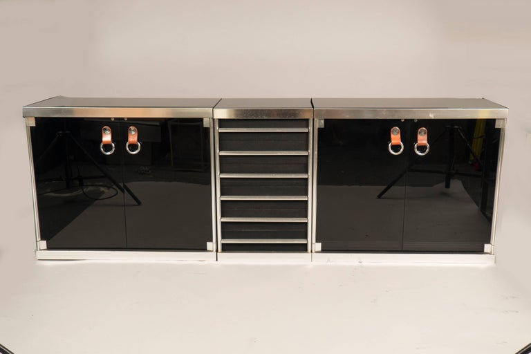 Steel and glass sideboard comprising two cabinets with smoked glass doors and leather pulls on each side, the middle features six drawers. New glass tops have been added.