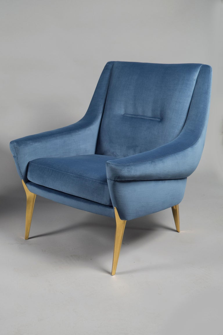 Over-upholstered armchairs with flared armrests, cushion seats and raised on feet of cast and gilded aluminum.   Measures; Height 32