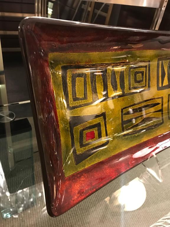 Reverse painted glass, the center part in gold paint with black design elements, the frame finished in a deep red. Signed.